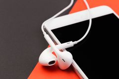 White earphones with phone on black and red background stock photography
