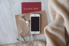 White earphones and white phone flatlay royalty free stock images