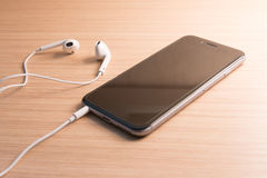 White earphones and smartphone Stock Images