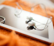 White earphones and tablet pc Stock Photos