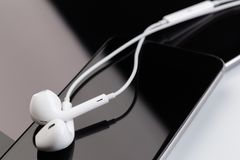 White earphones on tablet and phone royalty free stock photography