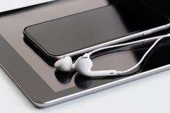 White earphones on tablet and phone stock photo