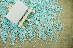 White easel with white paper for inscriptions on the crumbled blue gravel. Royalty Free Stock Photography