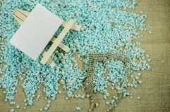 White easel with white paper for inscriptions with pearl beads and brilliant necklace. White easel with white paper for inscriptions on the crumbled blue gravel Royalty Free Stock Photos