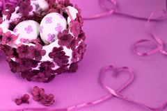 White Easter basket with eggs, decorated with flowers on the background with a ribbon in the shape of a heart. Pink hues. White Easter basket with eggs royalty free stock image