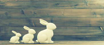 White easter bunnies. Retro style picture. White easter bunnies on rustic wooden background. Retro style toned picture Royalty Free Stock Photos