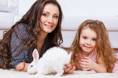 White Easter bunny. Beside happy mother and daughter stock image