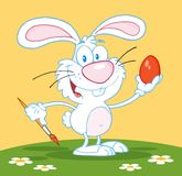 White easter bunny painting an egg outdoors Stock Image