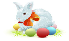 White easter bunny sitting on green grass. Bunny and colored Easter eggs Stock Photo