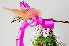 White easter egg with bird painted on white glossy stone on grassy surface with korbash in background Stock Image