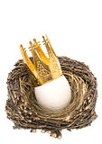 White easter egg with golden crown decoration. In wooden nest isolated on white background Stock Images