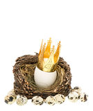 White easter egg with golden crown in nest. White easter egg with golden crown decoration in nest isolated on white background. selective focus Stock Photography