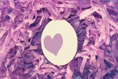 White Easter egg with a light purple heart on the background of the purple nest of decorative purple grass. Easter decoration. Decoration for Easter stock photos