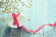 White easter egg with plaid ribbon. Small white flowers on rustic wooden table Royalty Free Stock Image