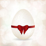 White speckled egg and red ribbon background Royalty Free Stock Images