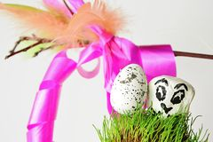 White easter egg and stone with bird face on grassy surface with traditional korbash whip in background Stock Photo