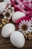 White Easter Eggs Ornement. With flowers and ribbons on rattan background Stock Photography
