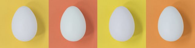 White Easter eggs on a banner with pastel multicolour squares. Four white Easter eggs on a banner with pastel multicoloured squares royalty free stock image