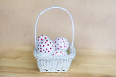 White easter eggs  with red dots in small white basket Royalty Free Stock Image