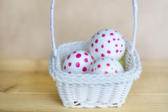 White easter eggs  with red dots in small white basket Stock Photos
