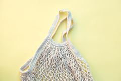 White eco-friendly string bag isolated on yellow background, responsible consumption stock photography