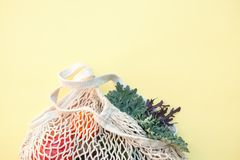 White eco-friendly textile string bag with fresh fruits, herbs and vegetables from local farmer market  on yellow backgrou. Nd, plastic free shopping, healthy stock photo