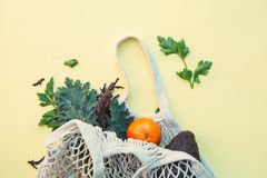White eco-friendly textile string bag with fresh fruits, herbs and vegetables royalty free stock photos