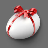 White Egg. Beautiful white egg wrapped in red ribbon Stock Photo