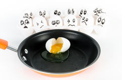 White egg broken in skillet with eggs with faces scared. Royalty Free Stock Photo