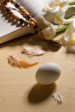 White egg, chicken feathers, bible with rosary and flowers Royalty Free Stock Image