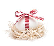 White egg in a nest with red ribbon and bow Royalty Free Stock Photos