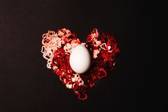 White egg on red heart. stock photography