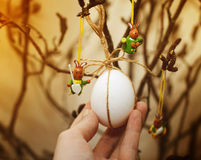 White egg in the shell and three small different wooden rabbits Royalty Free Stock Images