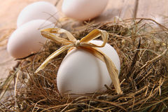 White egg with straw bow in nest Royalty Free Stock Image