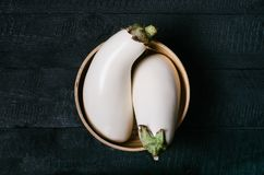 White eggplant on textiles with dry grass in a round bowl on wooden mock up, vintage black space background. Of old dark boards top view, vegan food on table Royalty Free Stock Photo