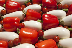 White eggplants red bell pepper tomato background Stock Images