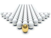 White eggs aligned forming an arrow with golden egg Stock Photography
