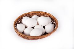 White eggs in a basket. On white Stock Images