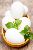 White eggs in basket. White eggs on wood table Royalty Free Stock Photography