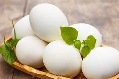 White eggs in basket. White eggs on wood table Stock Photos
