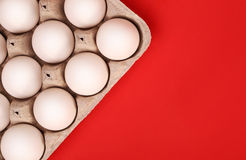 White eggs in the box over red Stock Photography