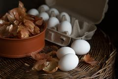 White eggs  in a box with a yellow onion peel  in a dish on a wicker tray prepared for coloring in organic dye for Easter stock photos