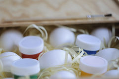 White eggs and colored paints. White eggs and colored paints in a wooden box Stock Photography