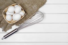 White eggs corolla. On a white wooden background Royalty Free Stock Images