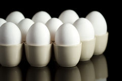 White eggs in egg-cups on black 2 Royalty Free Stock Images