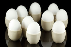 White eggs in egg-cups on black 3 Royalty Free Stock Photo