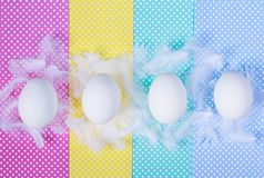 White eggs and feathers on colorful polka dots background. Happy Easter concept. Minimal style, flat lay. Close up. White eggs and feathers on colorful polka royalty free stock photography