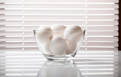 White eggs in glass bowl. Closeup of glass bowl full of raw eggs over jalousie on window background Royalty Free Stock Photo