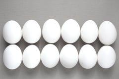 White eggs on a gray background. A dozen white eggs on a gray background Stock Image