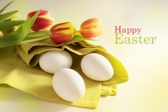 White eggs in a green napkin and red tulips, text Happy Easter, Stock Image